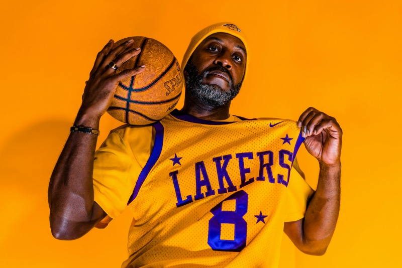 older man wearing a lakers jersey, holding a basketball