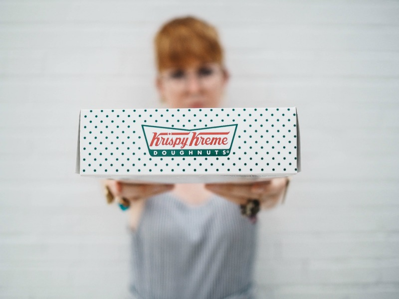 woman holding krispy kreme box