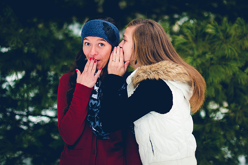girl telling another girl a secret